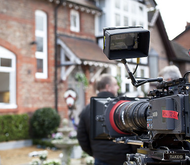 Camera on set with a house in the background