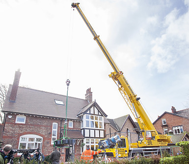 Large crane and entire house in view