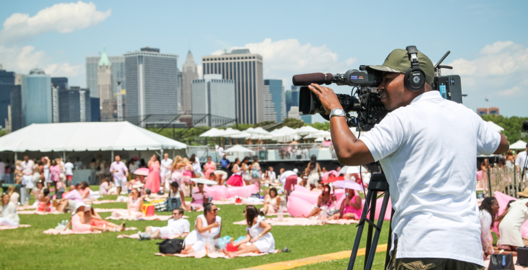 Cameraman filming at a festival with the New York skyline in the background