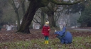 Girl with red jacket in field with animated pet dinosaur