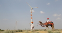 wind turbine and someone riding a camel