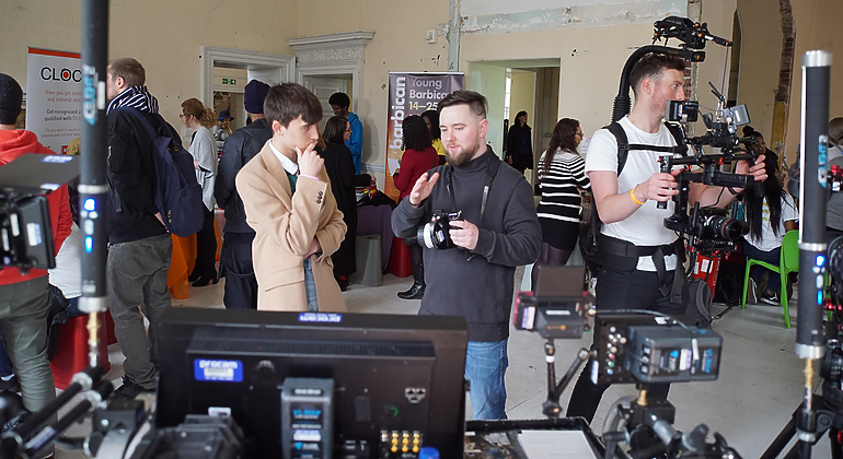 Exhibition area with attendees interacting with Procam staff