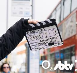 Clapperboard in front of London bus with Headliners title