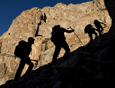 Mountaineers and scientists on expedition trekking up a mountain