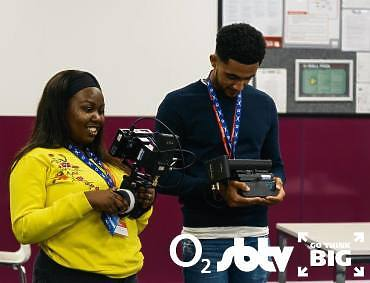 Two young people looking at ARRI Wireless Monitor and Lens Control System